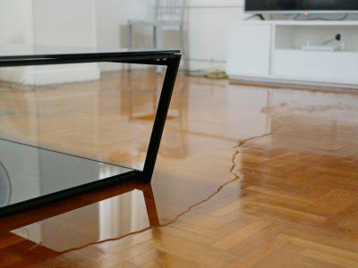 Flooded living room's hardwood flooring that needs water damage repair.